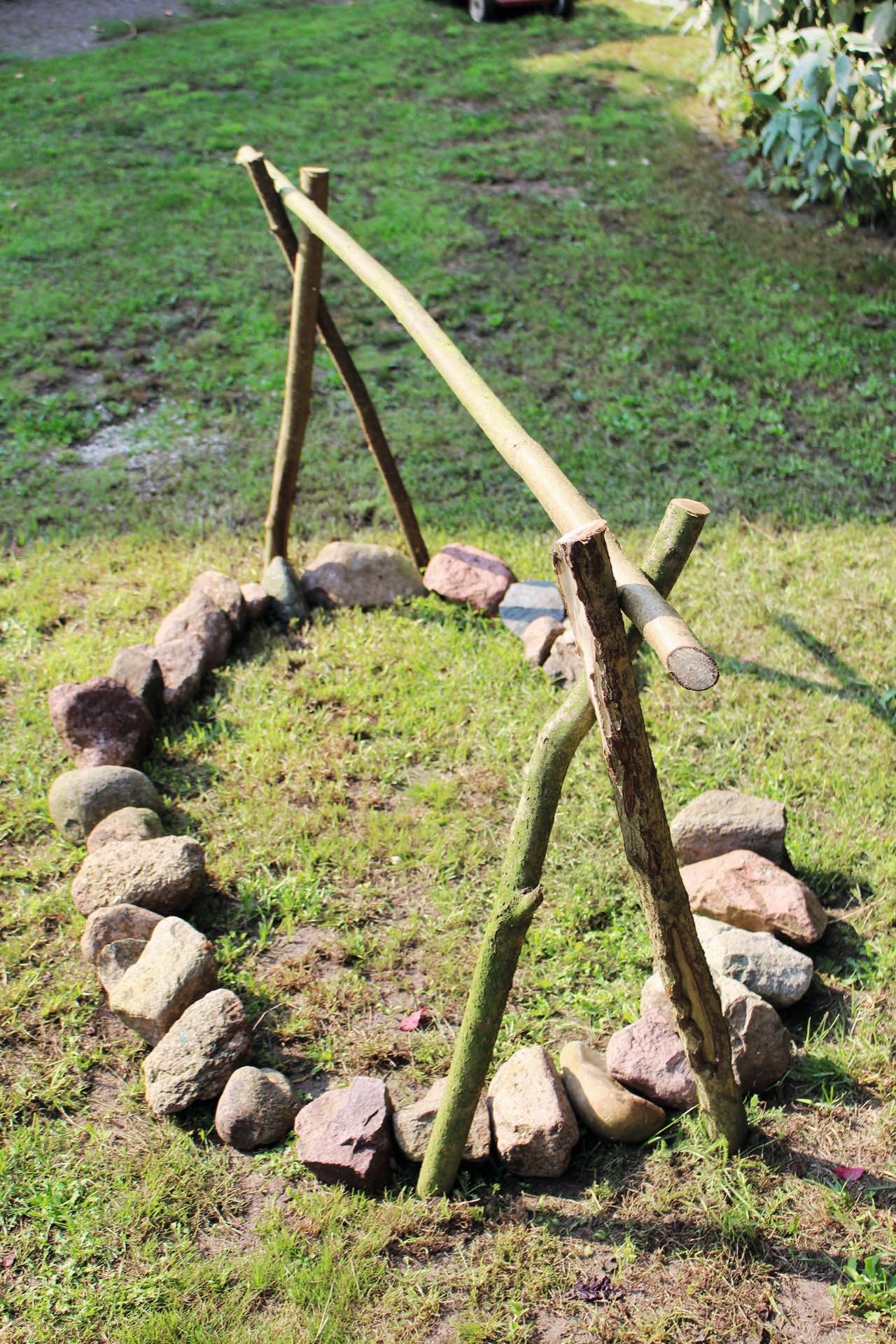 Gestell: hierfür finden Hasel- oder Buchenäste Verwendung. Wichtig: Diese müssen grün sein! Vier dieser Äste werden etwa 25 Zentimeter tief in den Boden getrieben. Auch wenn es nicht so aussieht, dieses Gestell gibt für unser Vorhaben ausreichend Halt.